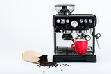 Isolated black manual coffee maker with grinder and red coffee mug and bag of freshly roasted coffee beans on white background, front view
