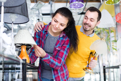 Girl and man in shop of home appliances are choosing night lamp