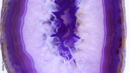 Texture of a dark purple agate piece on a white background