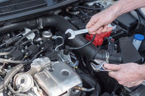 Hands of car mechanic working on car engine Poster
