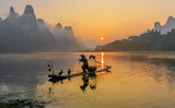 Cormorant fisherman stands on the ancient bamboo boat with lamp and birds in the sunrise - The Li River, Xingping, China