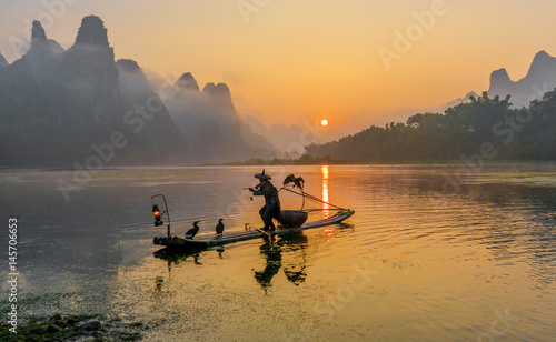 Poster Guilin Cormorant fisherman stands on the ancient bamboo boat with lamp and birds in the sunrise - The Li River, Xingping, China