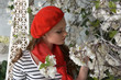 A girl in a red beret in the spring