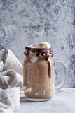 Chocolate coffee milkshake with ice cream scoop served in glass mason jar on gray texture background. Summer sweet drink