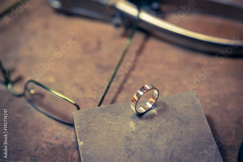 Working desk for craft jewelry making. Final wedding ring product on the table. © zphoto83