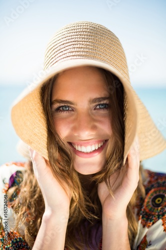Portrait of happy young woman wearing hat at beach