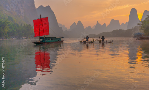 Foto op Canvas Guilin Fisherman sits on traditional bamboo boats at sunrise (boat with a red sail in the background) - Li River, Xingping, China