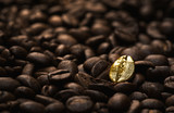 Fototapety Individuality concept, close up of a single bright, gold coffee bean over many dark ones with copy space