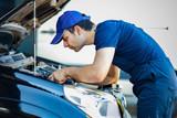 Mechanic fixing a car engine - 145741015