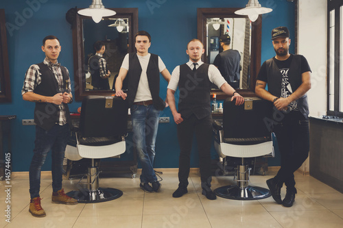 Male team of barbers at modern barbershop