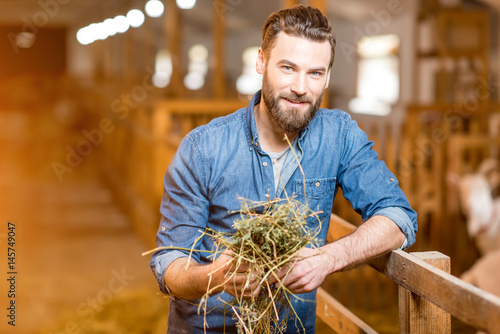 Portrait of a handsome farmer standing with hay in the goat barn. Natural milk production and farming
