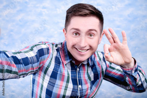Poster Selfie photo of attractive confident young man in plaid shirt showing ok gesture