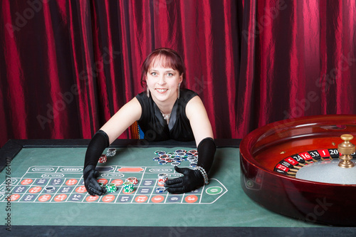young woman wearing  black gloves and black dress wins in a casino Obraz na płótnie