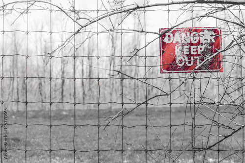 Red Danger sign posted to barbed fence tangled in branches, warning people to ke Poster