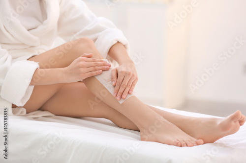 Young woman depilating legs with wax in spa center