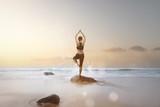 Frau macht Yoga-Übungen am Strand