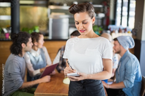 Beautiful waitress standing by customers in restaurant