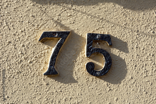 House number 75 sign on wall Poster