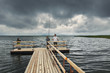 Dramatic landscape with wooden pier and fishermen