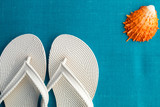 White flip flop near seashell on blue background. Top view. - 145947070