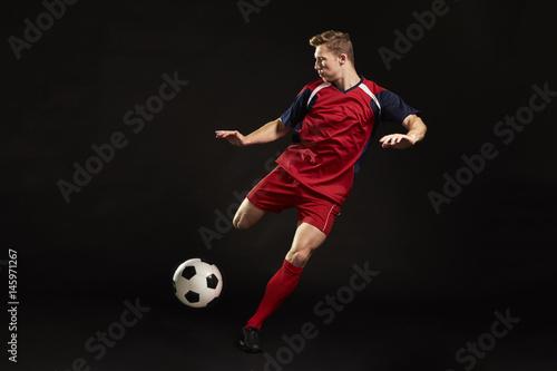 Fotobehang Voetbal Professional Soccer Player Shooting At Goal In Studio