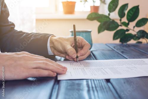 Mężczyzna prawnik lub urzędowe podpisuje dokumenty za pomocą pióra