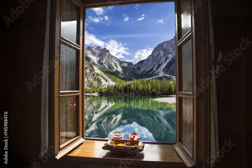 Fototapeta Window of an open house overlooking a lake in the mountains