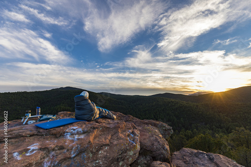Foto op Canvas Cappuccino woman in a sleeping bag looking out at the mountains