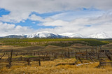 Abandoned Ranch Against Snow Covered Mountain Backdrop - 146009432