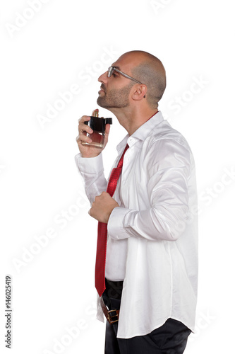Young man puts perfume on a white background