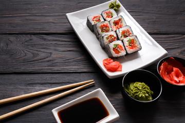 Set of sushi rolls on black wood background, closeup