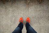 Fototapety Man with orange shoes standing on a textured, concrete city street.