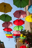 Multicolored umbrellas on street.
