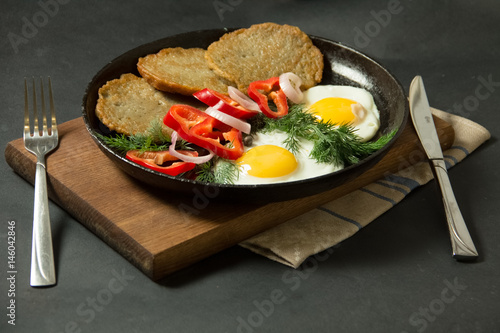 Homemade food. Tasty breakfast. Appetizing fried egg with potato pancakes and herbs in dripping pan  on a black background - 146042846