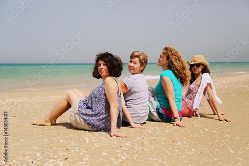 Portrait of four  40 years old women walking on seaside Poster