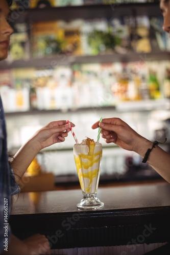 Poster Milkshake Couple having milkshake at counter