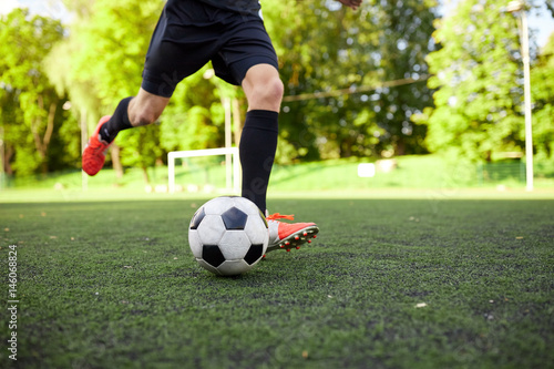 soccer player playing with ball on field Poster