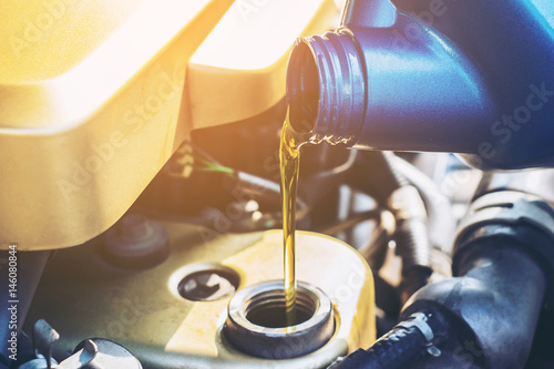 mata magnetyczna Pouring oil to car engine, close up selective focus