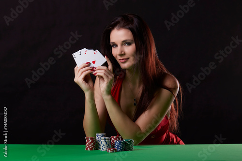 young brunette woman playing poker on black background плакат