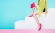 Beautiful legs woman with pink heels shoes and purse handbag sitting on the white steps isolated on light blue background