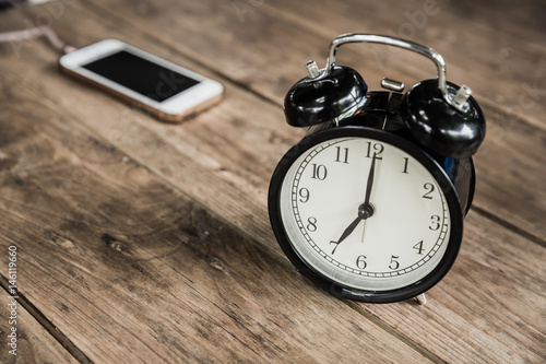 Poster clock times at 7 o'clock morning on wood table with smart phone charging at cafe blur background