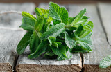 Close-up of a bunch of fresh green peppermint on an old wooden rustic table. Food and health care background. - 146124868
