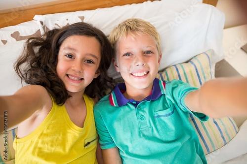 Plagát Smiling siblings taking selfie in bedroom