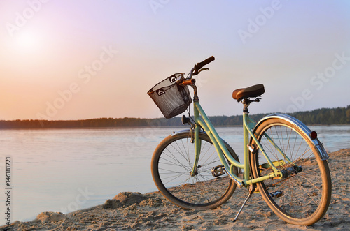 In de dag Fiets Vintage bicycle with a basket near the lake during beautiful summer sunset. Copy space.