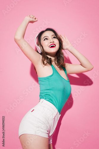 Beautiful asian girl with professional makeup and stylish hairstyle singing and dancing while listening to music on pink background.