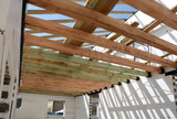 The wooden structure of the building. Wooden frame building. Wooden roof construction. photo for home. house building. Installation of wooden beams at construction the roof truss system of the house. - 146200884