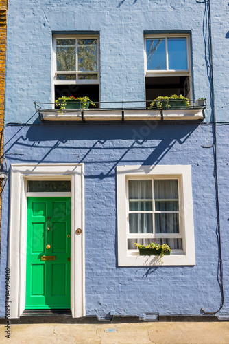 Light blue restored Victorian British house facade exterior with green door and Poster