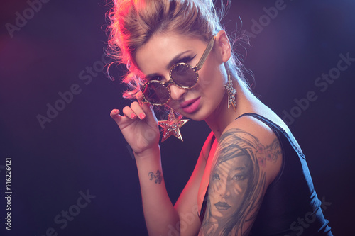 Portrait of sexy tattooed woman posing in the light flashes in studio Poster