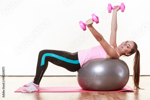 Sporty girl with pink dumbbells.