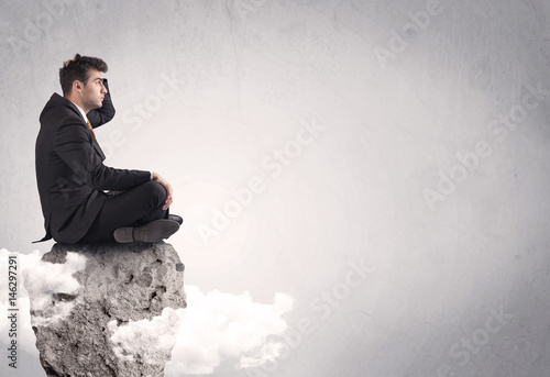Office worker sitting on top of a rock